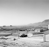 A black and white photograph of a lone car parked in a cul de sac, with houses and mountains in the background.