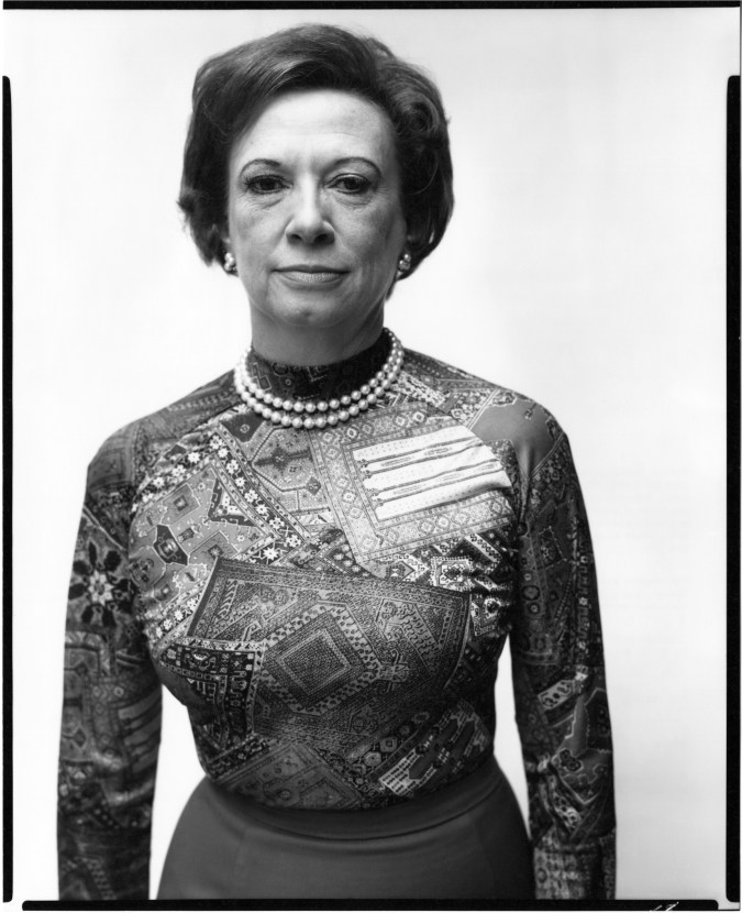 Black and white photograph of a woman wearing a bold-patterned shirt and two small pearl necklaces