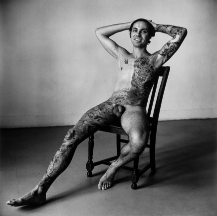 Black-and-white photograph of a seated nude man with a tattooed leg and half-torso with his hands behind his head