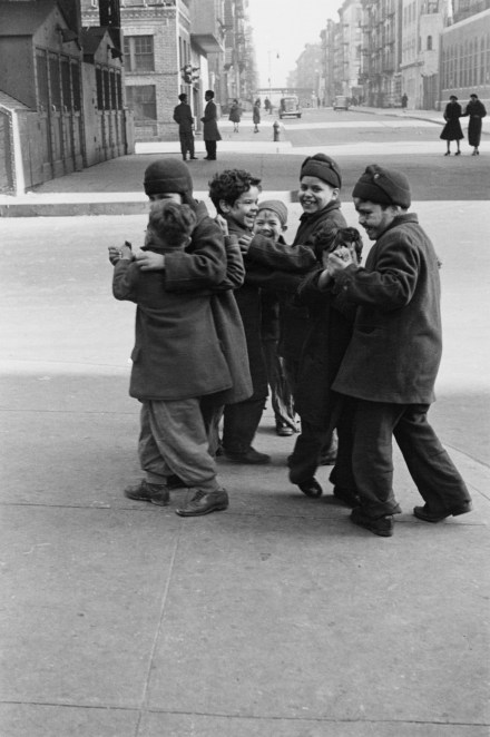 Black and white photograph of a group of children in oversized coats walking down a city sidewalk