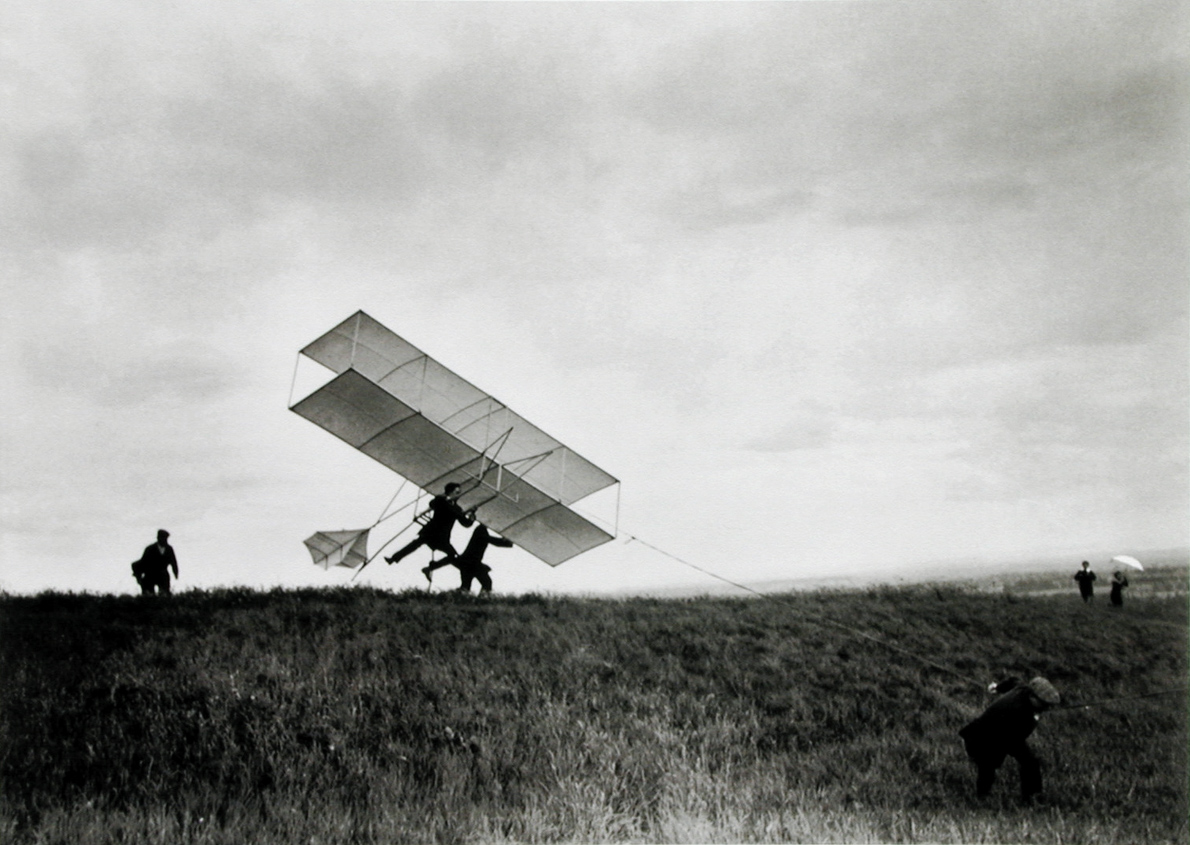 Black and white photograph of people launching an early airplane by hand in an open field