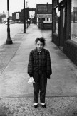 Black and white photograph of a young girl standing on an empty sidewalk
