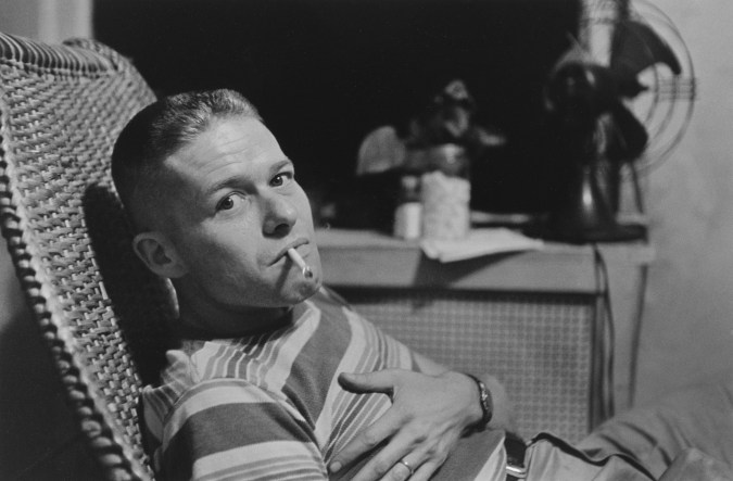 Black and white photograph of a seated man smoking a cigarette turning his head to the camera