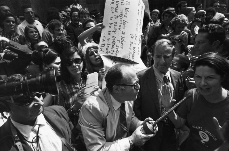 Black-and-white photograph of a man interviewing a woman speaking in a crowd of people