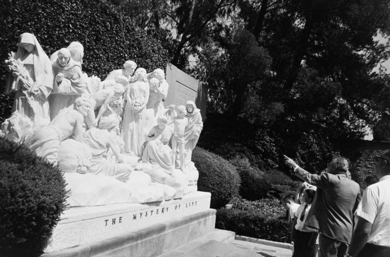 Black-and-white photograph of a man pointing out a large group memorial sculpture titled THE MYSTERY OF LIFE to a small group
