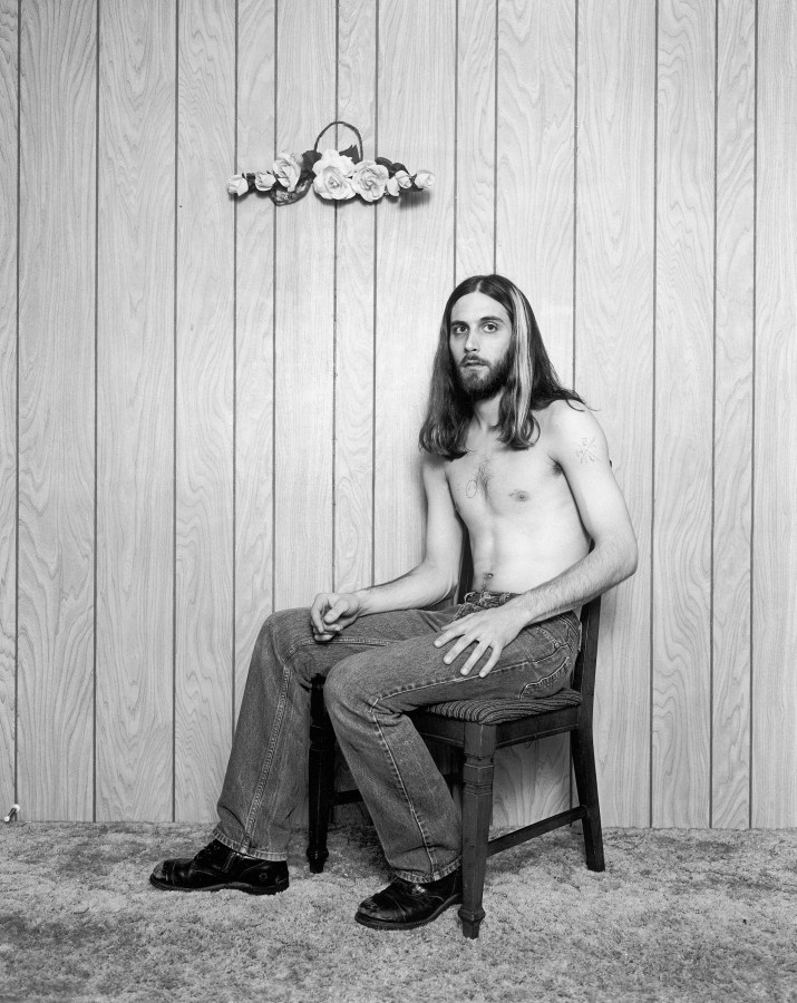 Black-and-white photograph of a shirtless man with long hair seated in front of a wood paneled wall