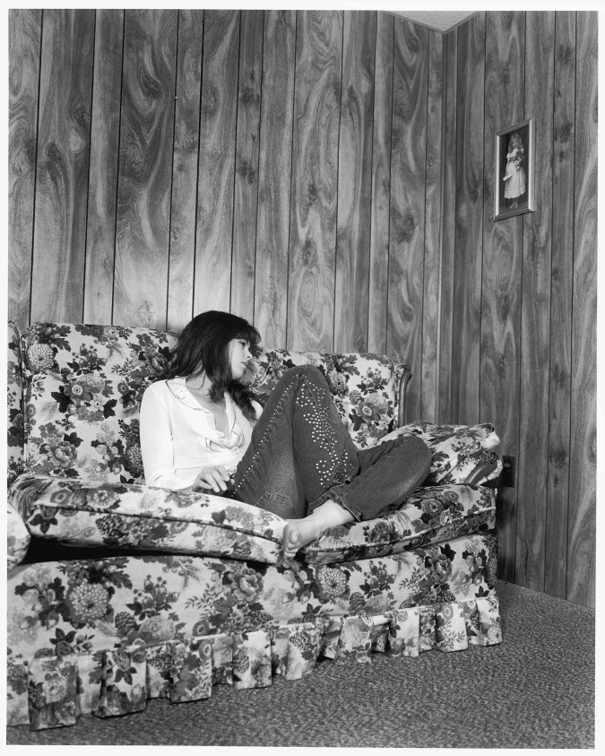 Black-and-white photograph of a woman seated on a flowered sofa in a wood paneled room