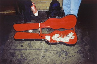 A color photograph of an open red-lined guitar case on the sidewalk, in front of two pairs of legs.