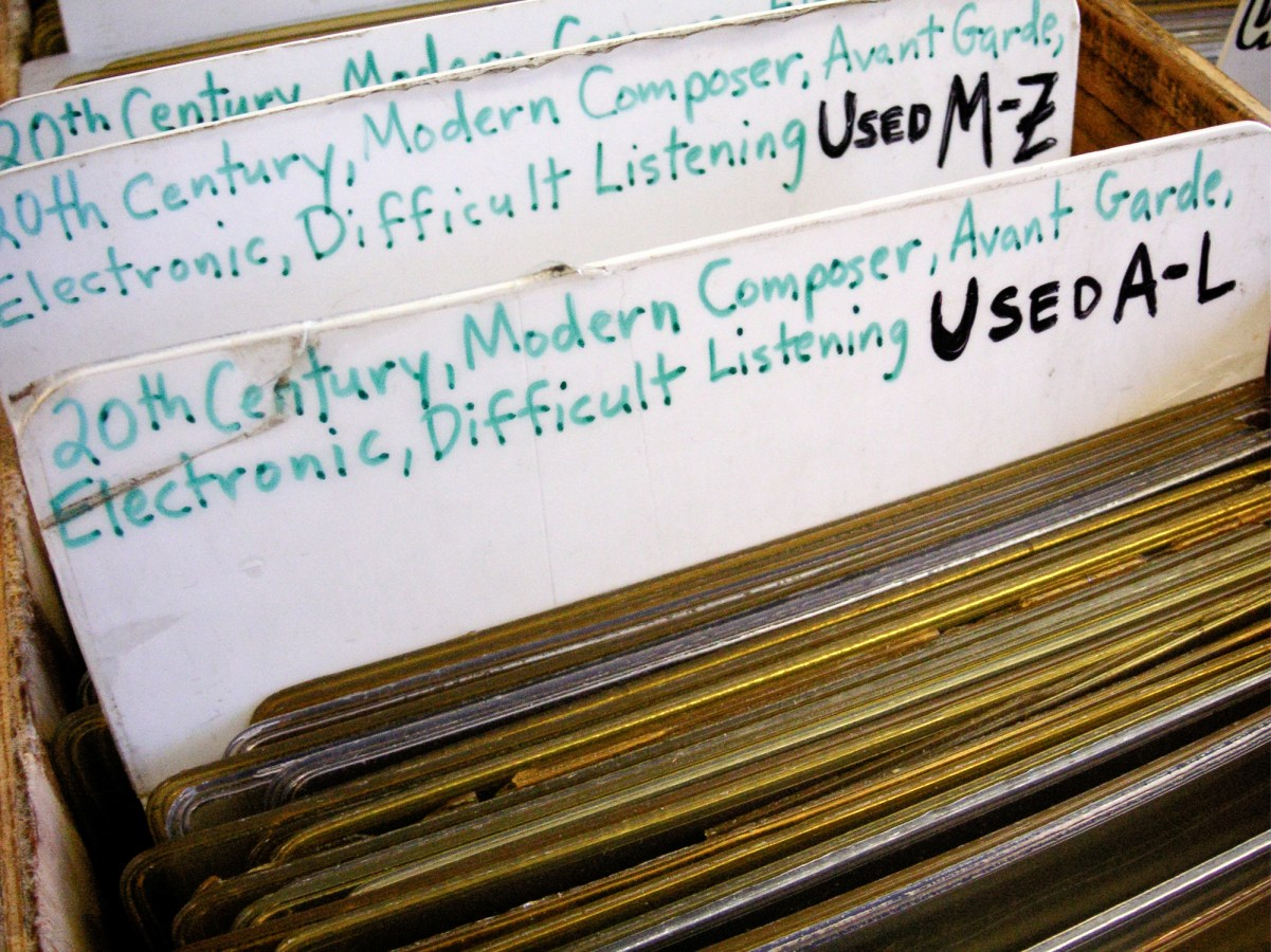 A color photograph of dividers in a bin at a record store, labeled with the genres of the records.