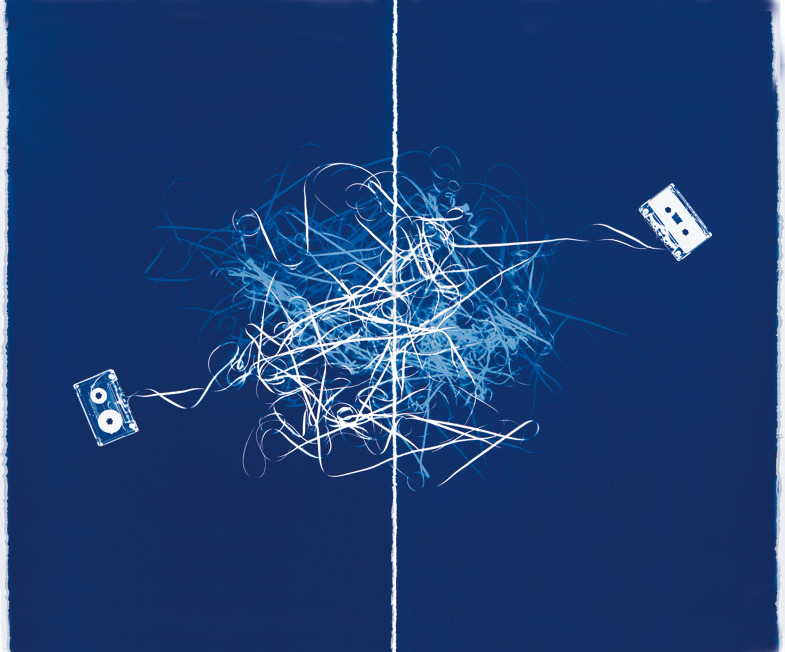 Horizontal image of the white tapes of two cassettes tangling in the middle on a deep blue background