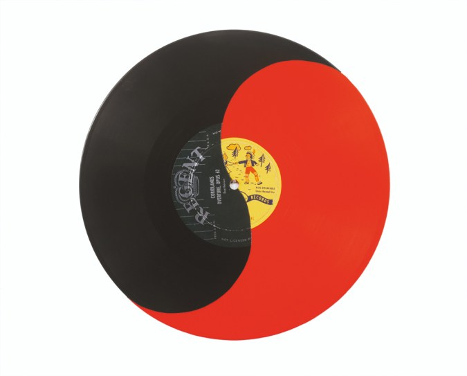 A red vinyl record with half painted black to create a yin-yang motif