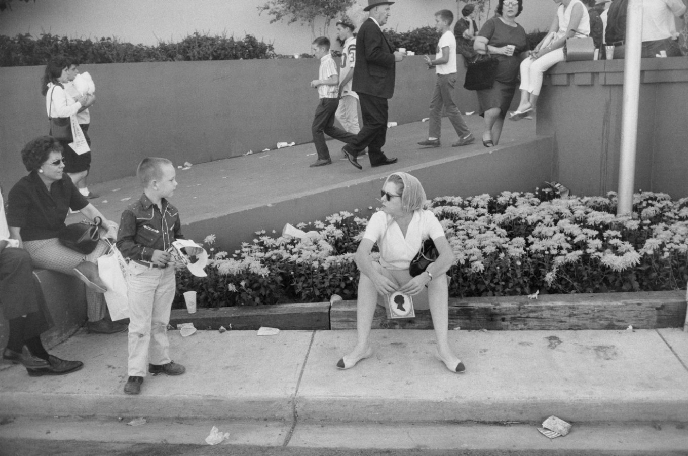 Black-and-white photograph of a woman sitting on a curb holding a cameo portrait and looking at a young boy