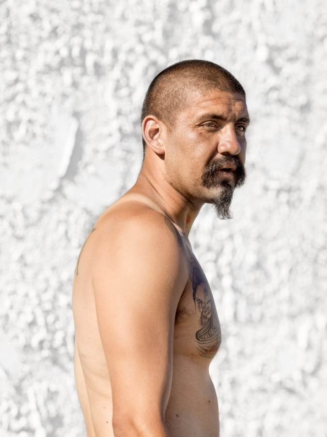 Color photographic portrait of a shirtless man turned sideways standing in front of a white stucco wall