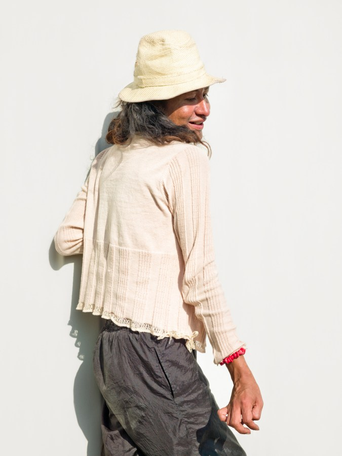 Color photograph of a woman in a white top and hat with her head turned back over her shoulder