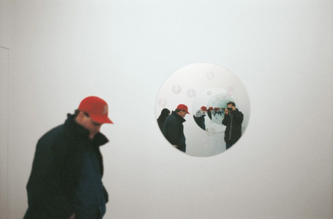 An installation shot of a person in front of a circular mirror on a white wall reflecting him and the mirror behind him