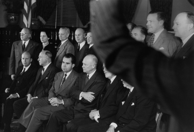 Black-and-white group portrait of politicians in two rows with raised arm in the foreground