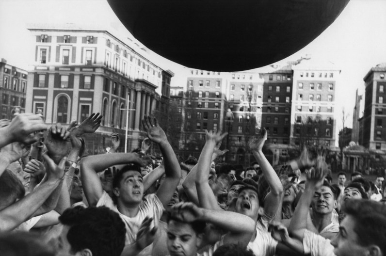 Black-and-white photograph of a crowd of young men with arms raised towards a round object floating above them