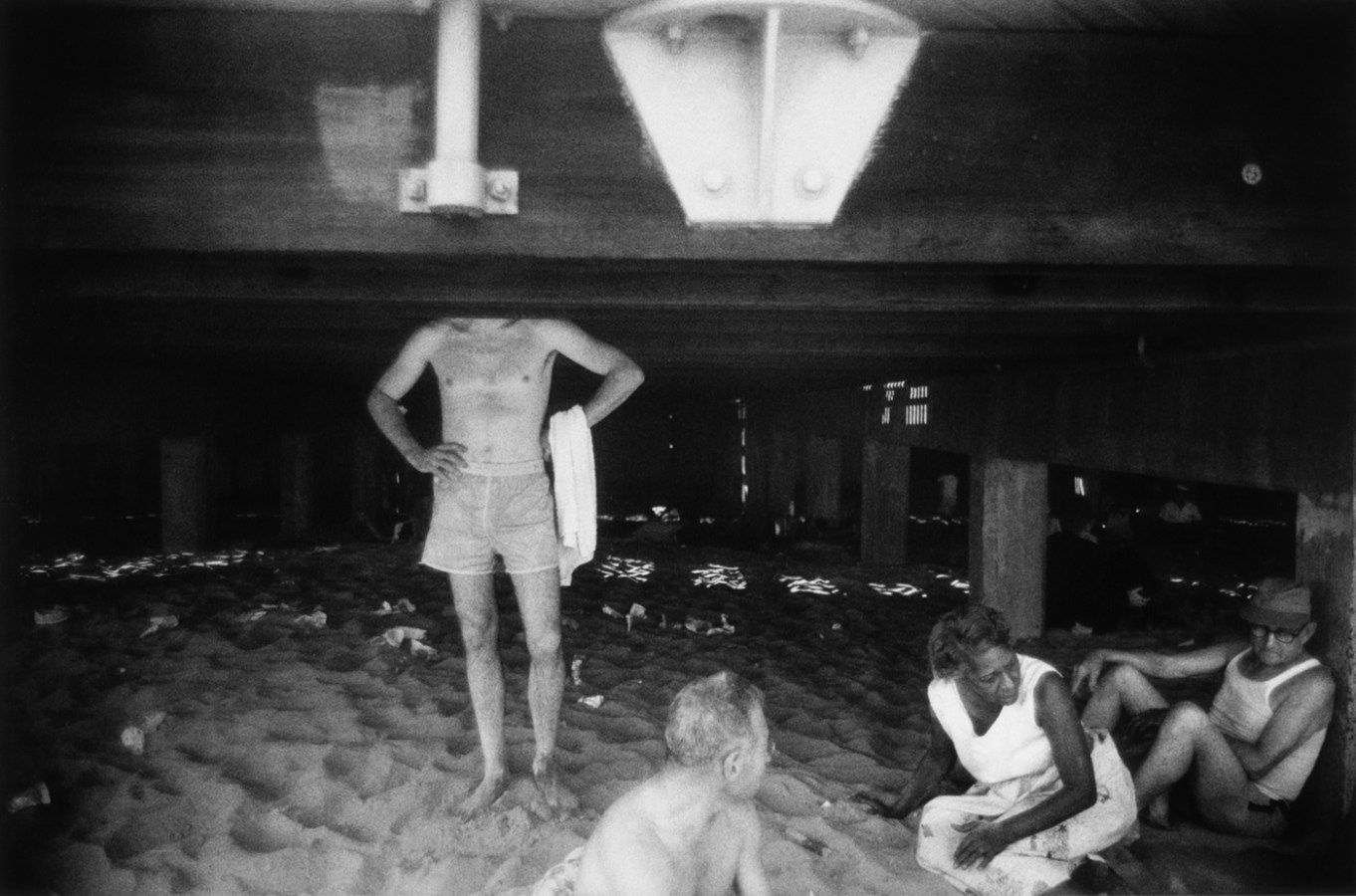 Black-and-white photograph of people in bathing suits beneath a boardwalk