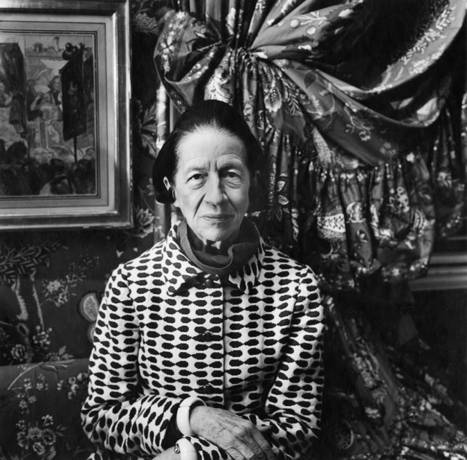 Black-and-white photograph of an older woman in a black-and-white patterned jacket standing in front of pinned-back floral curtains