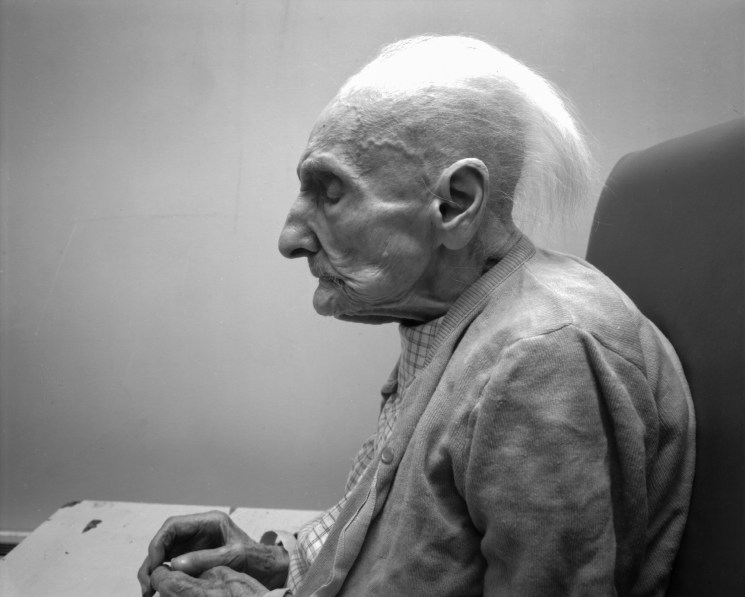 Black-and-white photograph of the profile of a seated elderly woman