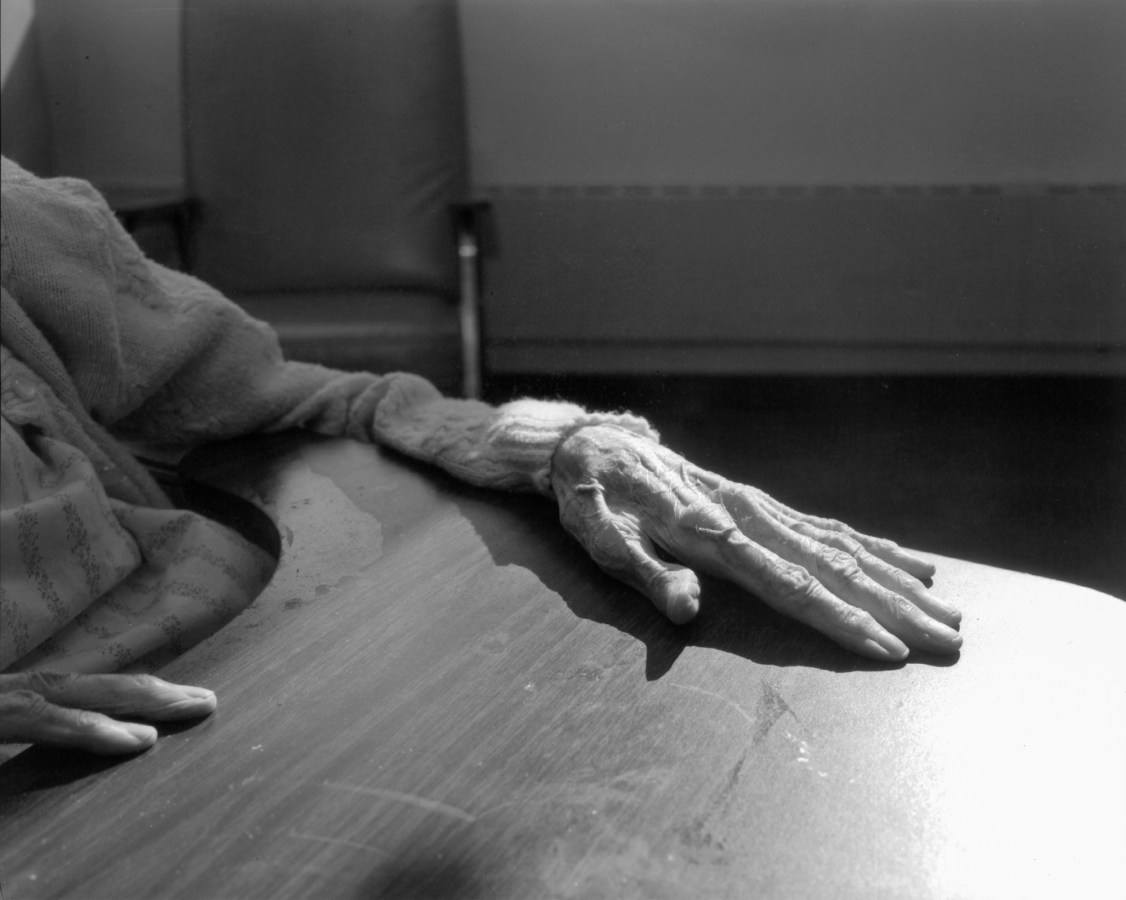 Black-and-white photograph of the hand of an elderly person resting on a tray table