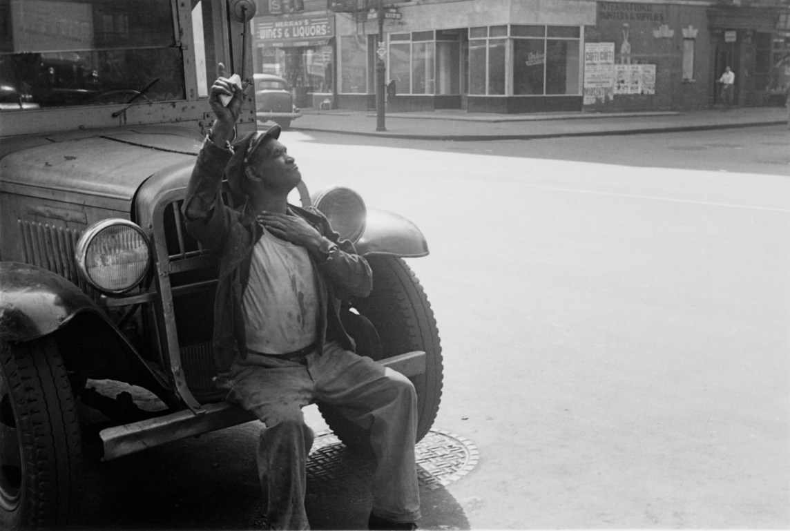 Black-and-white photograph of a man sitting on the front bumper of a vehicle with his arm raised