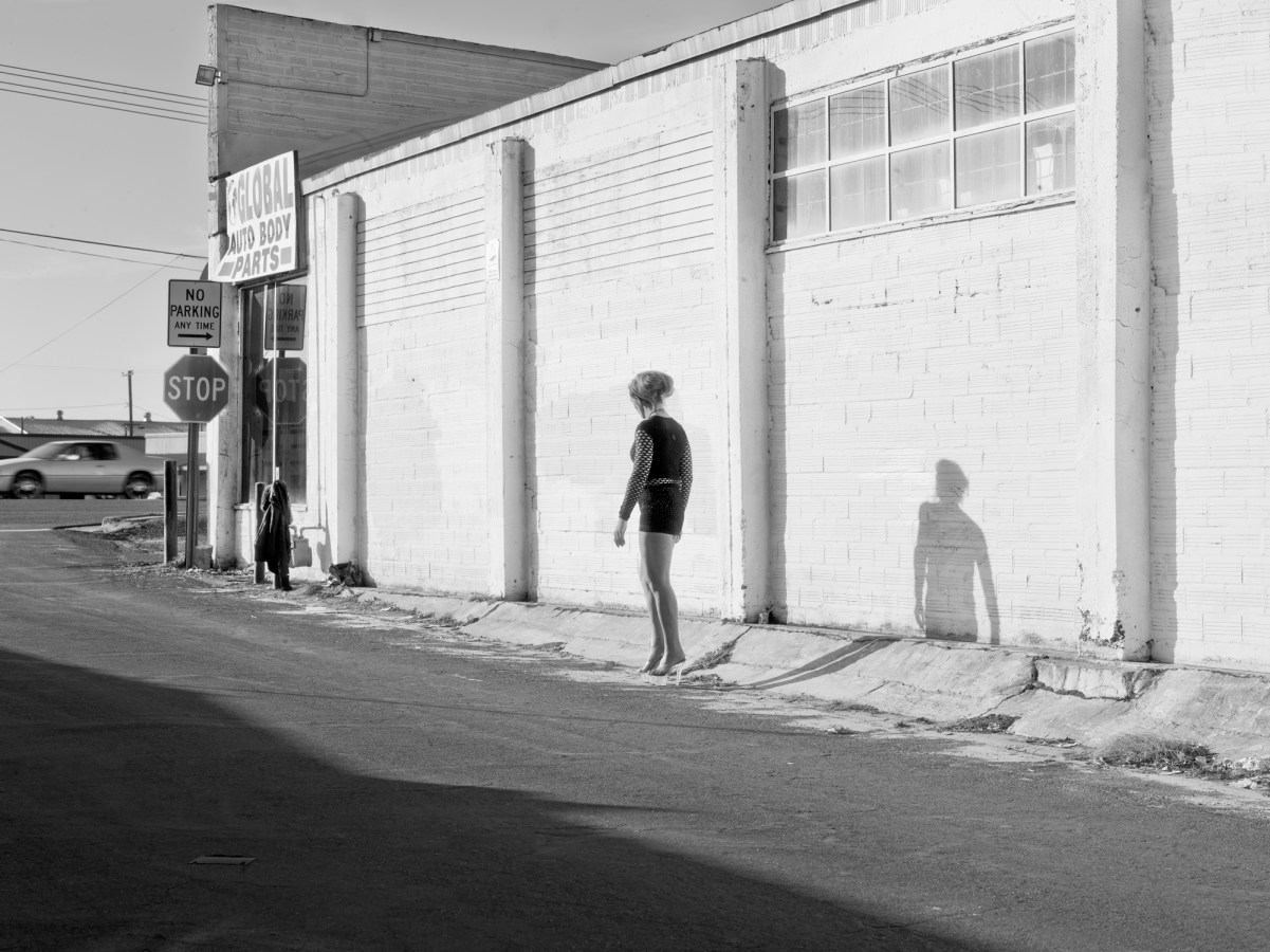 Black-and-white photograph of a woman walking by a low white building at an intersection