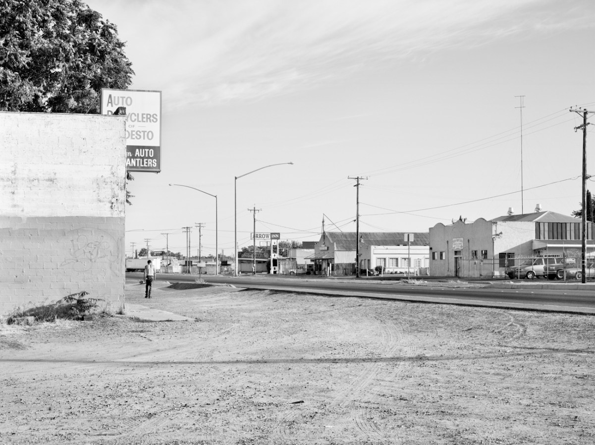 Black-and-white photograph of a dirt lot on a road with low buildings and a person walking away in the distance