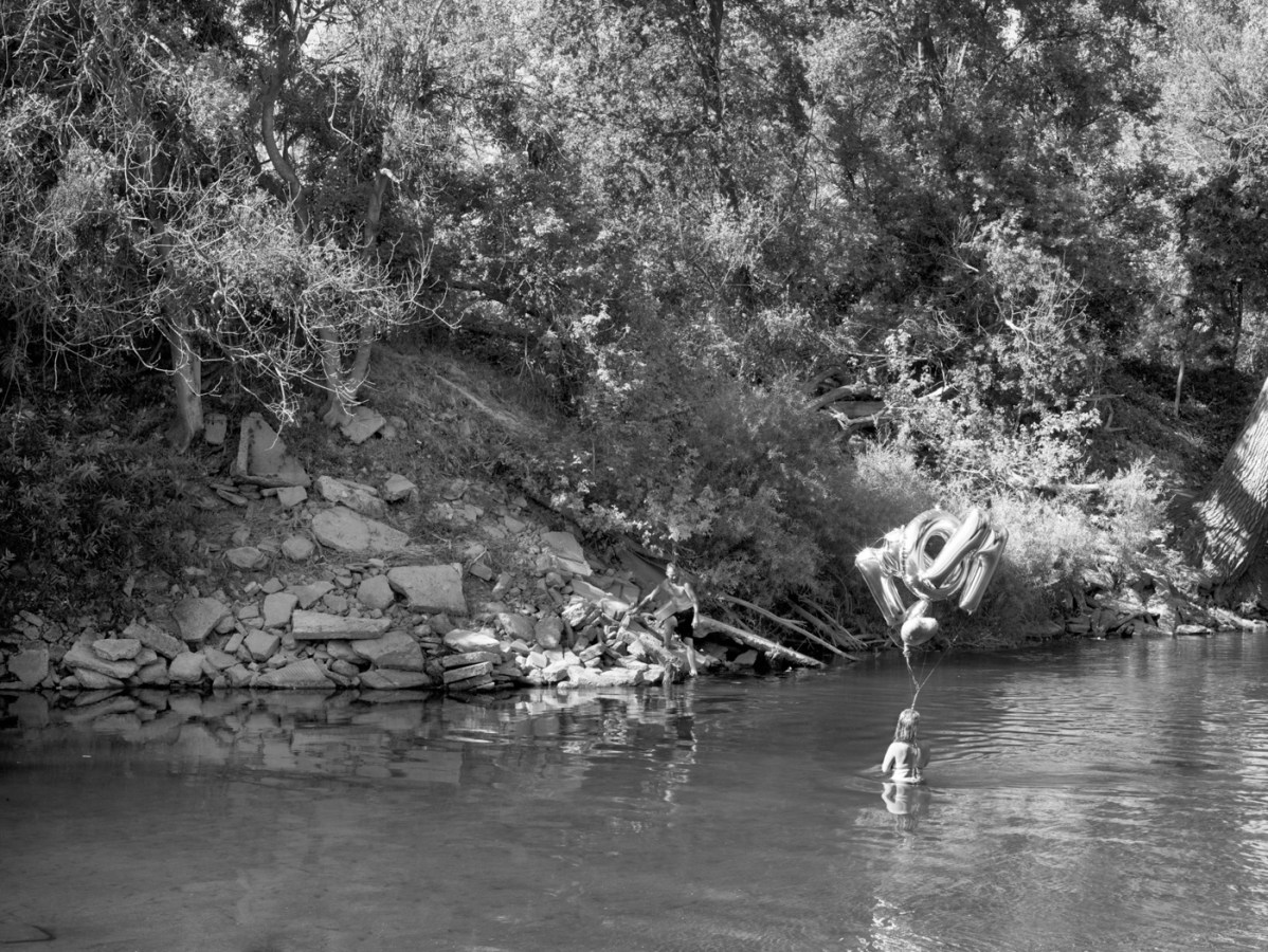 Black-and-white photograph of a man on on a rocky overgrown riverbank watching a woman standing in the water holding foil balloons