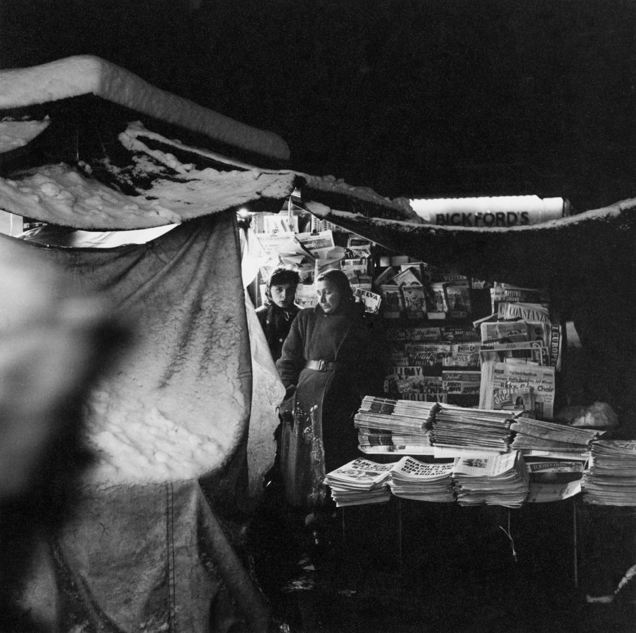 Black-and-white photograph of two women peering out from a snow-covered tent filled with stacks of newspapers