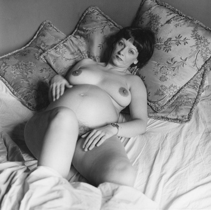 Black-and-white photograph of a pregnant nude woman reclining on a pile of pillows on a bed