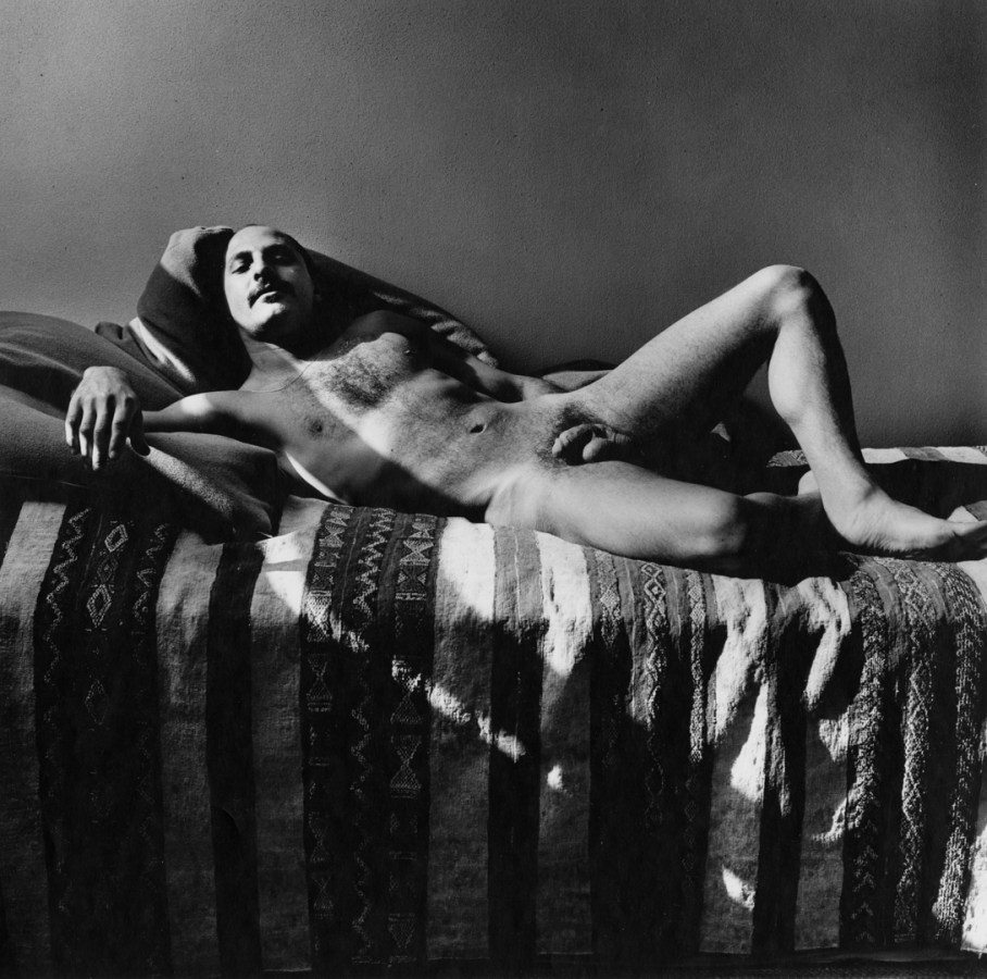 Black-and-white photograph of a reclining nude man on a bed