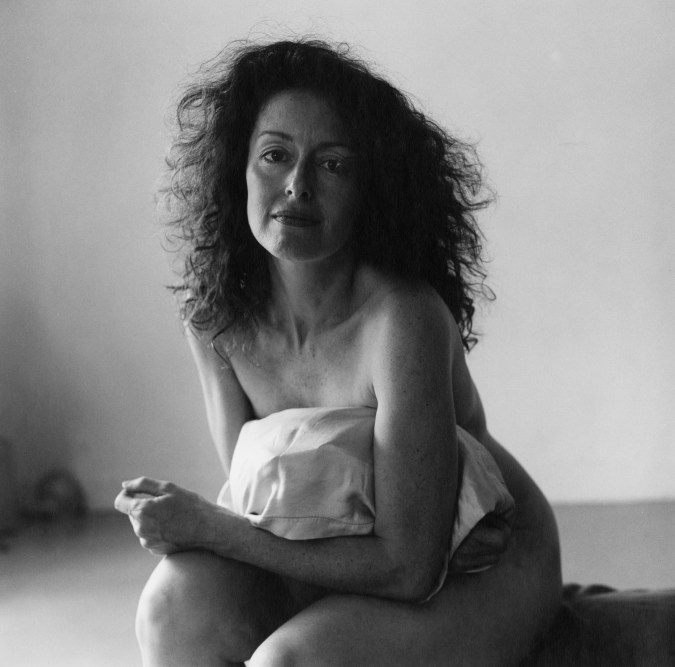 Black-and-white photograph of a seated nude woman holding a pillow on her lap