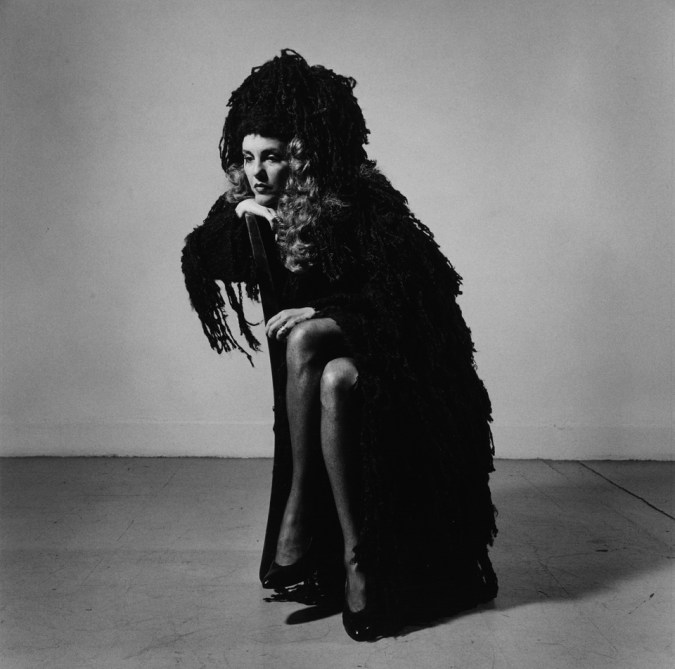 Black-and-white photograph of a woman with long curly hair in a dark wooly shawl seated sideways with her chin on her hand