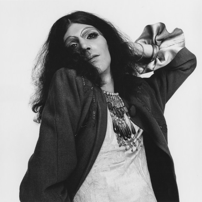 Black-and-white photograph of a person with long wiry black hair and heavy jewelry and make up with one hand behind their head