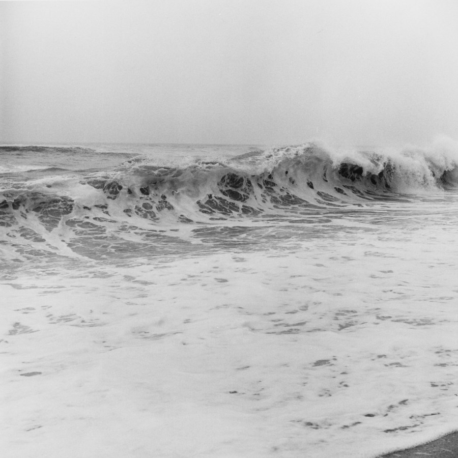 Black-and-white photograph of white water and a wave crashing on the seashore