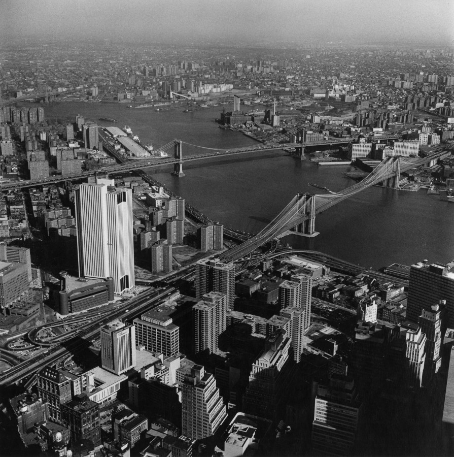 Black-and-white photograph of two bridges spanning a river between two cityscapes