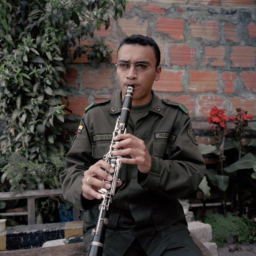 Color photographic portrait of a police officer seated in front of a brick wall playing an oboe