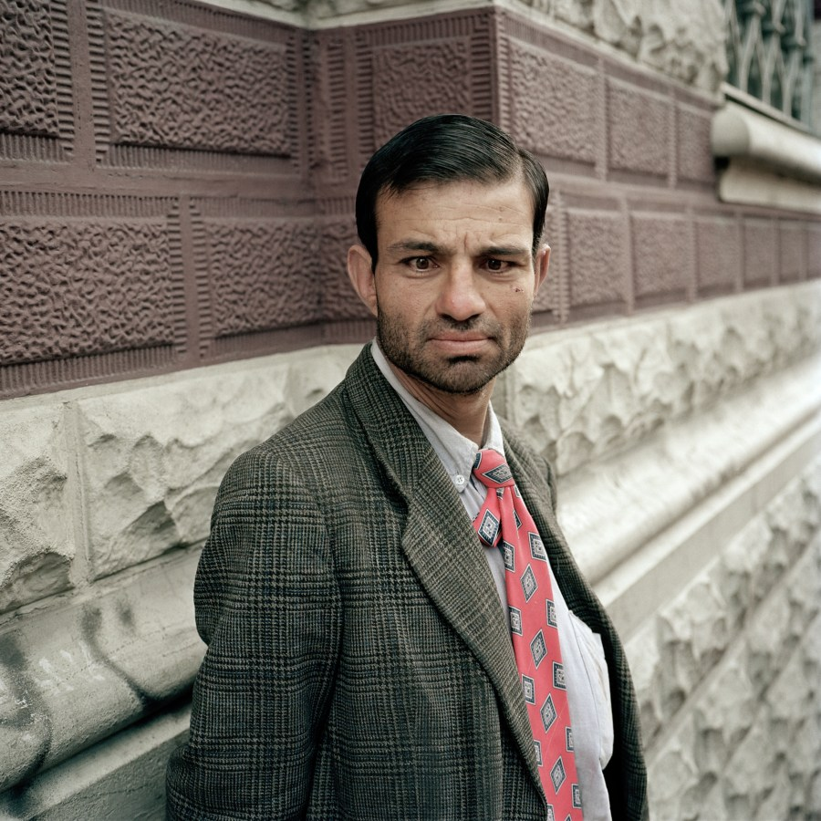 Color photographic portrait of a man in a tweed jacket and red tie in front of a stone façade