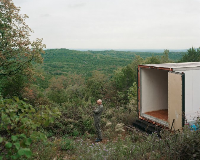 Color photograph of a bald man standing outside of an open box truck overlooking forested hills