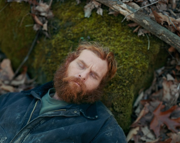 Color photograph of a red-haired and bearded man lying on a mossy ground with his eyes closed