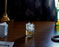 Color photograph of a glass of whiskey with ice on a dark wood desk