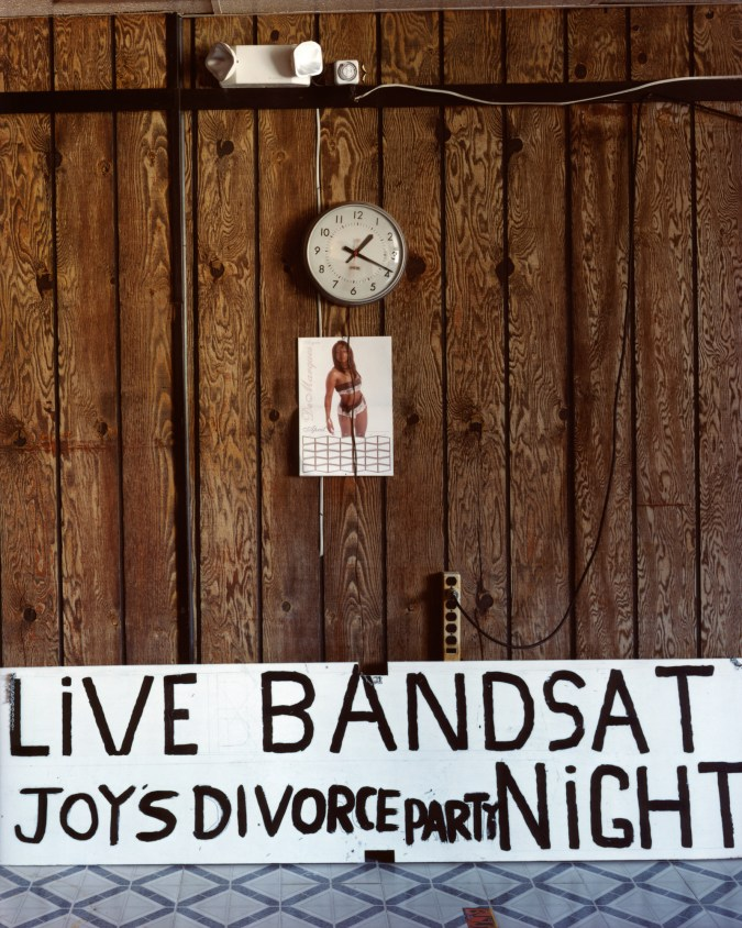 Color photograph of a wood paneled wall with a clock, picture of a woman in a bikini and hand-painted sign reading LIVE BAND JOY'S DIVORCE PARTY SAT NIGHT
