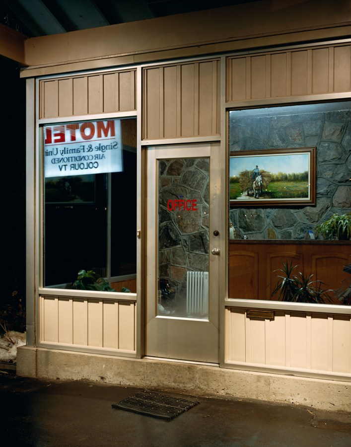 Color photograph of a motel's front office door at night, looking into a rock-paneled room with a framed picture of a man riding a hay wagon