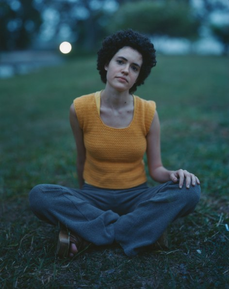 Color photograph of a young woman in a yellow knitted top sitting cross-legged on a green lawn at twilight