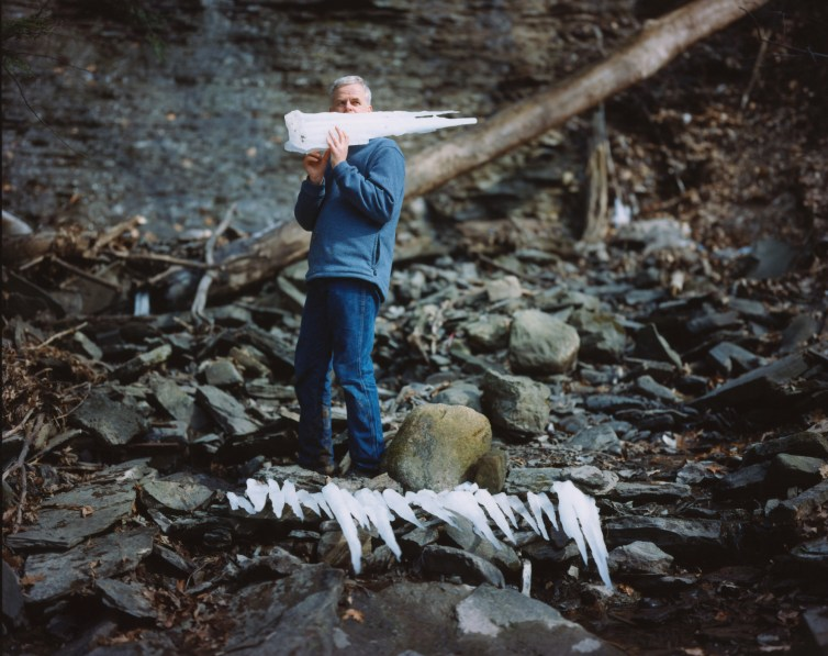 Color photograph of a man holding a large icicle on his shoulder standing behind a row of broken off icicles on the ground