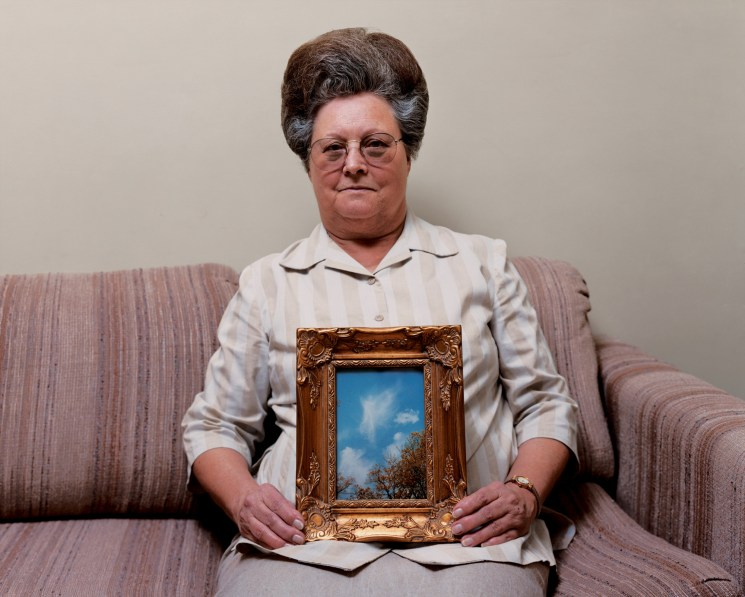 Color photograph of a woman on a couch holding a gilt-framed picture of trees under a blue sky on her lap