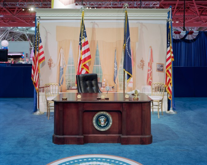 Color photograph of an empty set of the Oval Office with desk and painted backdrop in a convention hall setting