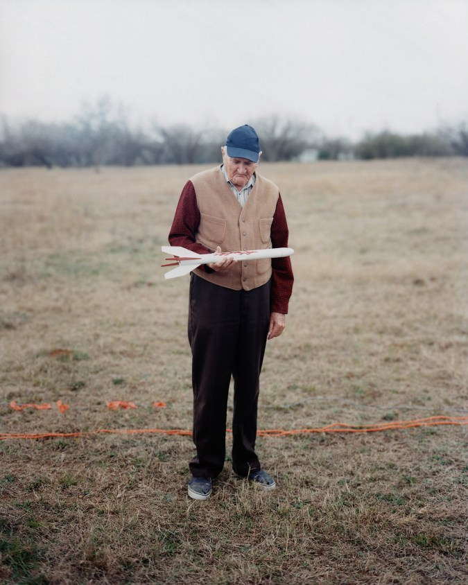 Color photograph of an elderly man standing on a brown lawn looking down at a model rocket in his hand