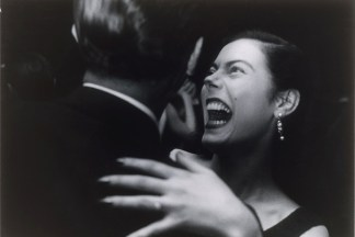 Black and white photograph of a couple in mid-embrace with the woman in mid-laugh